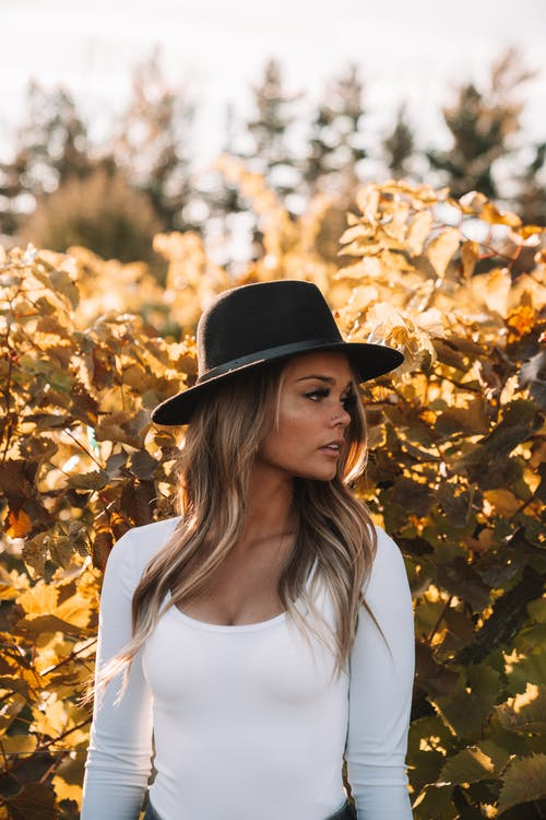 Woman in White Shirt and Black Hat Standing Near Brown Leaves