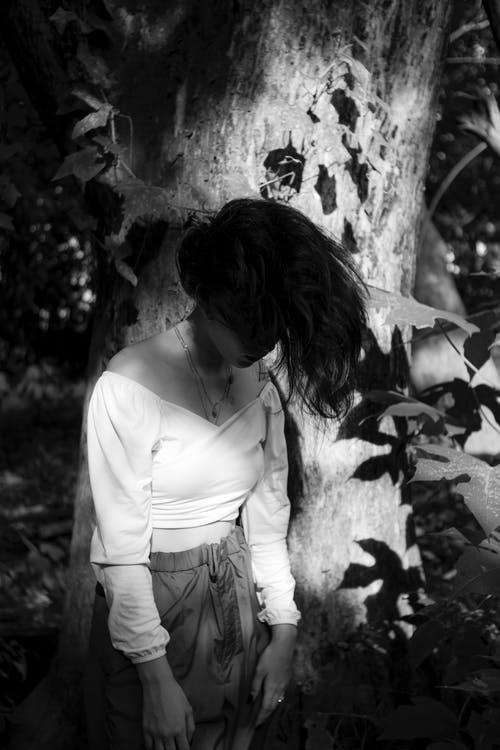 Anonymous upset woman covering face with hair in lush woods