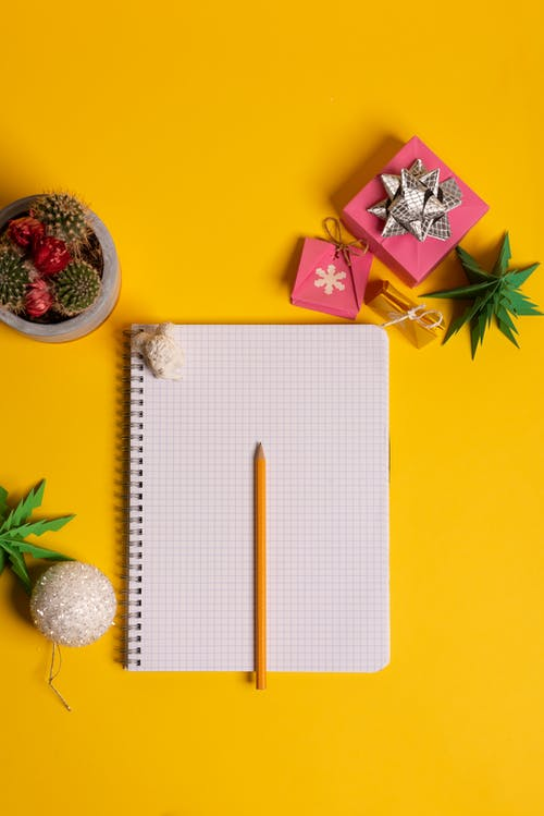 Notepad with pencil and present box on yellow background