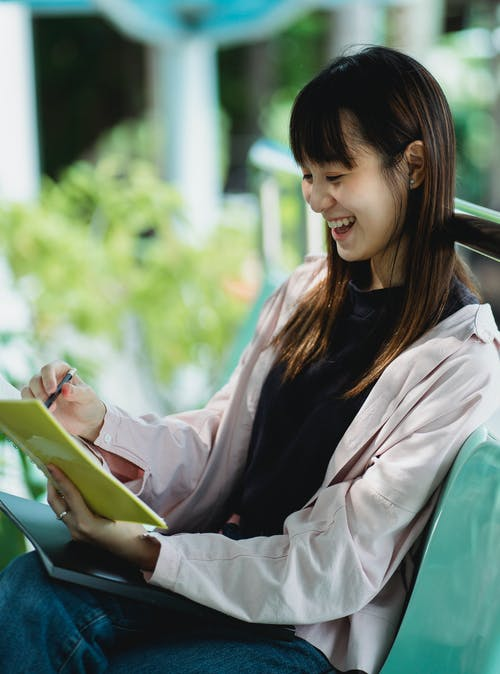 Cheerful ethnic teenager with exercise book studying on street