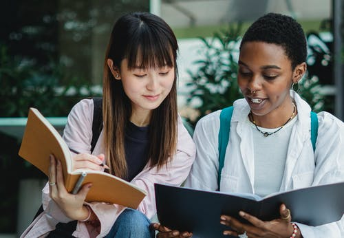 Young smiling black female student with exercise book talking to Asian partner on street in daylight