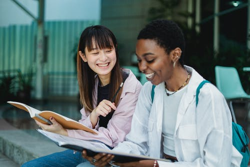 Young positive multiethnic female students with exercise books talking while doing homework on street stairs