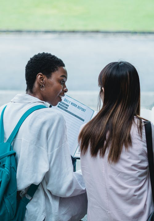 Black student with textbook speaking with anonymous ethnic partner outdoors
