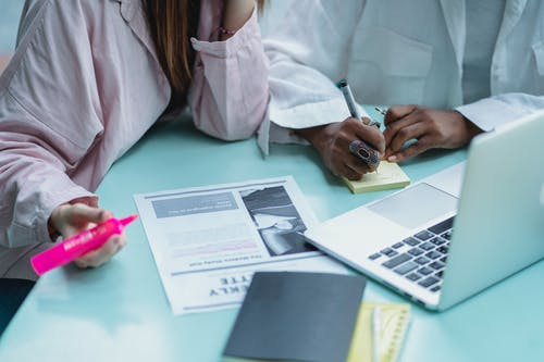 Crop multiracial students writing on sticky notepad near laptop