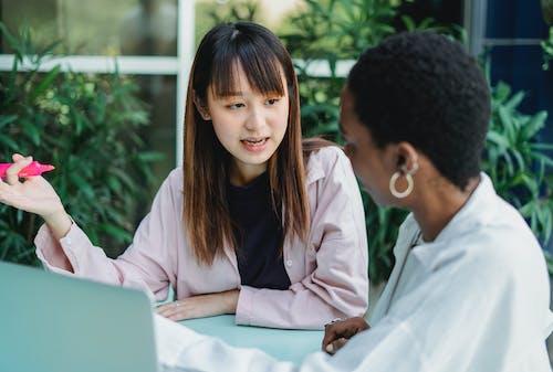 Asiatische Frau, Die Mit Schwarzer Freundin Am Tisch Im Garten Spricht