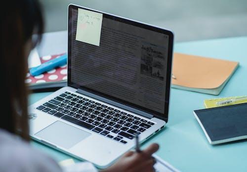 作物與筆記本電腦在桌旁學習的多民族學生