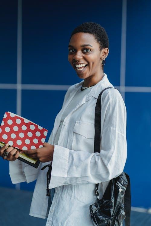 Веселый черный студент с тетрадями возле кафельной стены