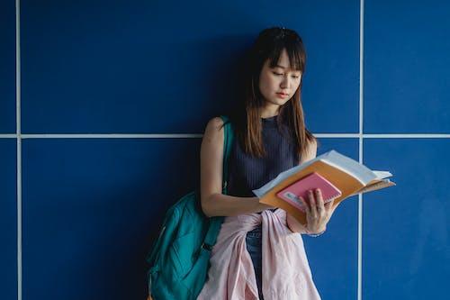 Fokussierter Asiatischer Student Mit Arbeitsbüchern, Die Nahe Blauer Wand Studieren