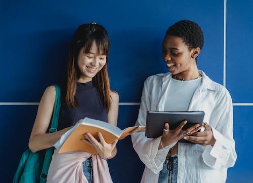 Fröhliche Gemischtrassige Freundinnen Mit Arbeitsmappe, Die Beim Lernen In Der Nähe Der Wand Interagieren