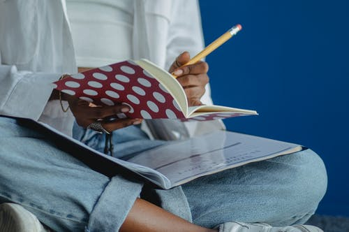 Crop anonymous diligent ethnic woman taking note with pencil in exercise book while studying with crossed legs on blue background