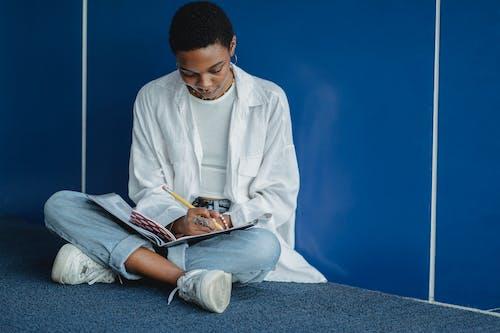 Học Sinh Dân Tộc Chăm Chú Viết Vào Sách Bài Tập Gần Bức Tường Xanh