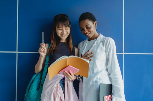 Young happy multiracial female students sharing workbook while studying together near blue wall in daytime