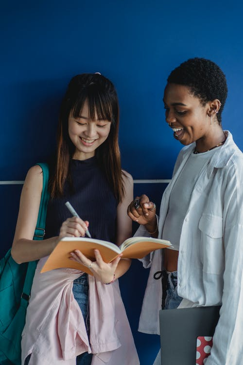 Young glad best diverse friends writing in exercise book while speaking near blue wall