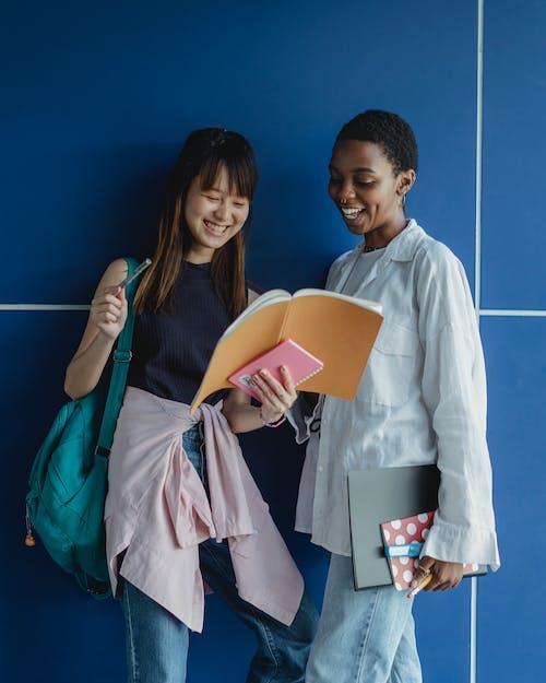 Smiling multiracial girlfriends sharing workbook while doing homework