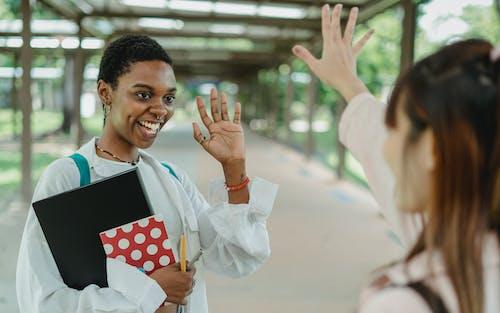 Estudante Negro Sorridente Dizendo Olá Para A Namorada Na Calçada