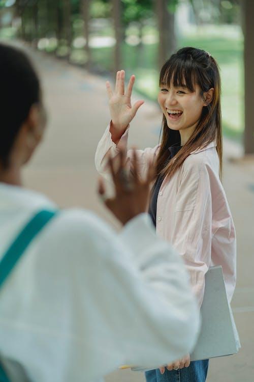 Fröhliche Asiatische Studentin, Die Ernte Schwarze Freundin Auf Straße Begrüßt