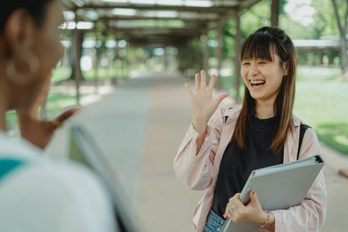 Young positive ethnic female student with folder greeting crop unrecognizable best friend on walkway while looking at each other