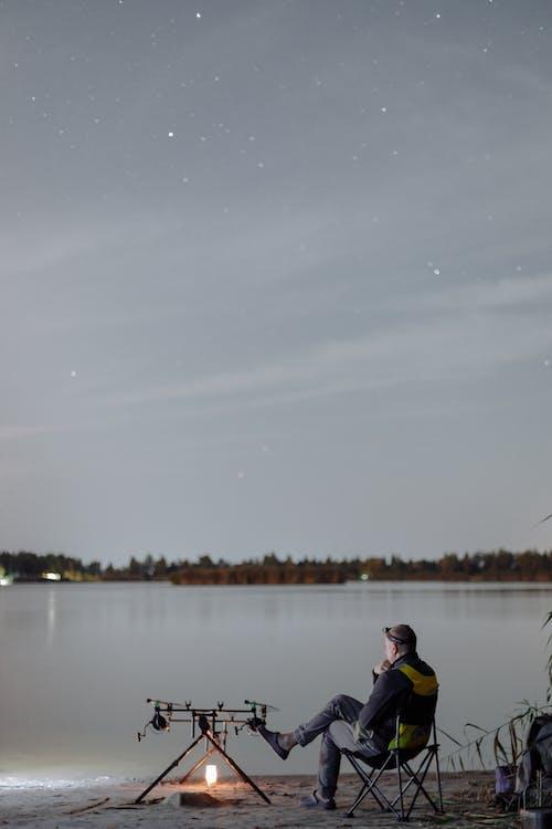 Человек в черной и розовой куртке, рыбалка на озере