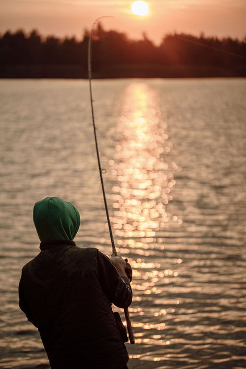 Person in Black Jacket and Green Knit Cap Fishing on Sea during Sunset