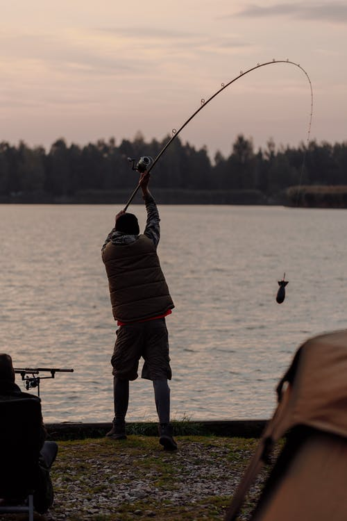 Man in Red Jacket and Blue Denim Jeans Holding Fishing Rod