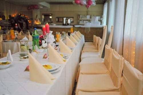 Rows of chairs and folded tissues on table in bright cafe