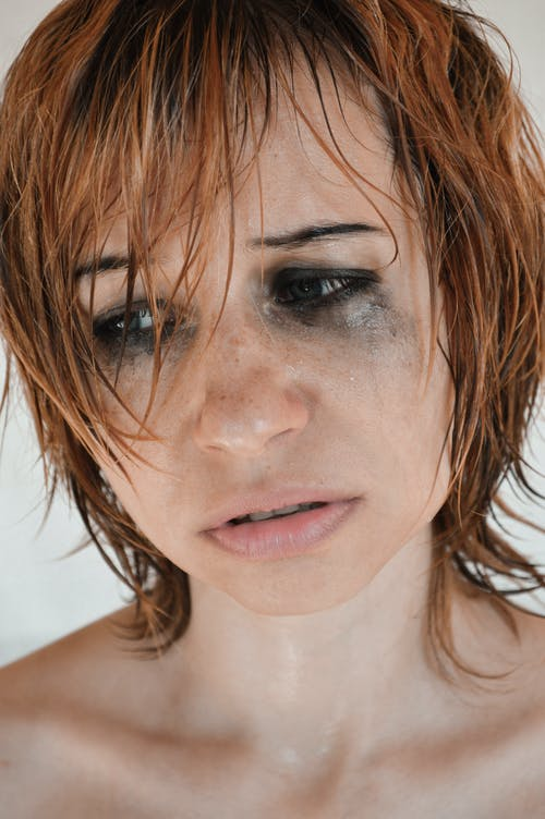 Crop desperate female with short hair bare shoulders and flowing mascara crying unhappily in studio