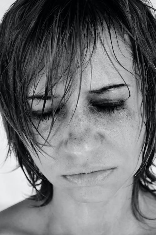 Black and white crop female with short hairstyle and bare shoulders frowning with eyes closed and crying in frustration