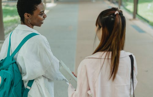 Crop black student speaking with anonymous girlfriend on pavement