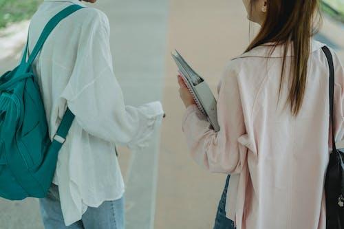 Crop unrecognizable female students strolling on walkway