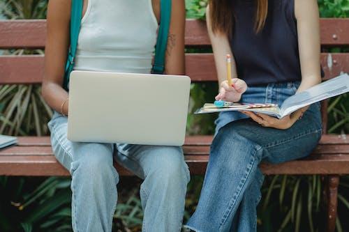 Estudiantes Femeninas Multirraciales Sin Rostro De Cultivo Usando Laptop En Banco