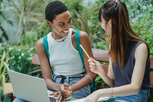 Joyful multiethnic female students working on assignment in park