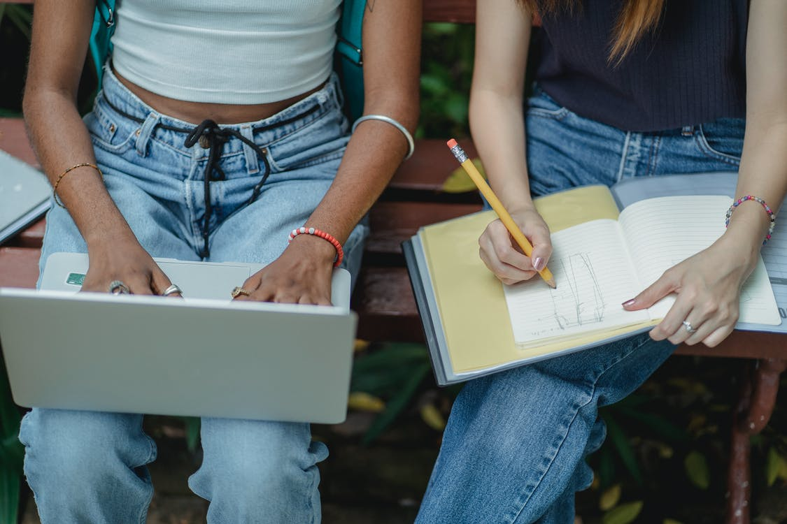 High angle crop faceless multiracial female friends typing on laptop and drawing in notebook with pencil while sitting on bench