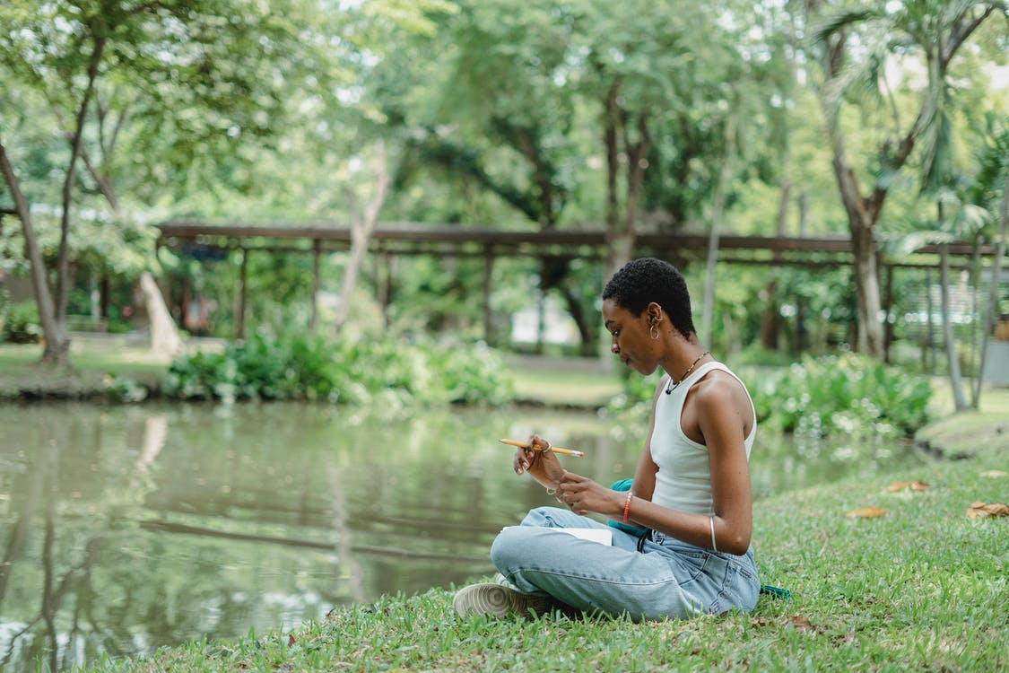Side view of young African American female wearing casual clothes sitting near pond on green grass and using notepad with pencil in summer day