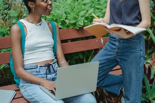 Crop multiracial female friends talking on bench in park while studying on computer and writing information in notebook