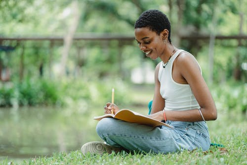 Black female writing in notepad while sitting on meadow
