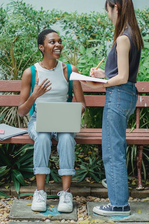 Full body multiracial female friends talking with each other outside while studying on netbook and using notebook while looking at each other