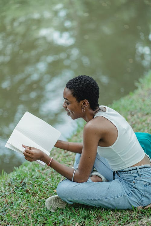 African American woman sitting on grass with sketchbook
