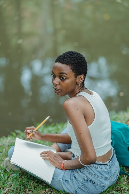 Full length of young African American lady with diary and pencil sitting near lake on green lawn in summer day while looking away