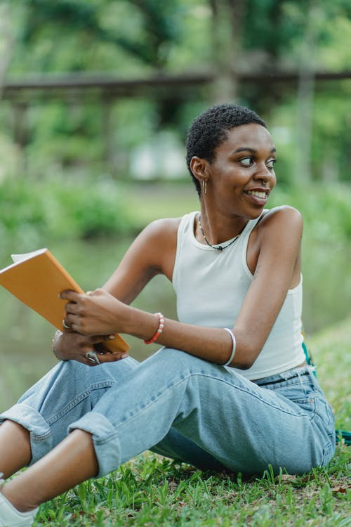 Young African American woman sitting near lake on green grass with sketchpad in summer day and wearing casual outfit while looking away