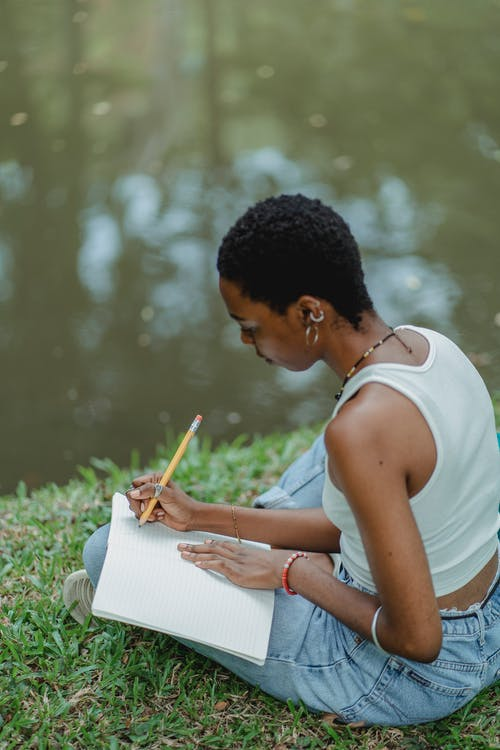 African American woman writing in diary on meadow