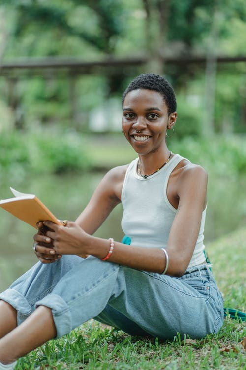 Black woman sitting on grass with notepad in hands