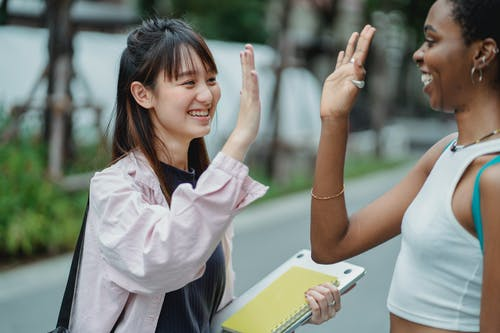 Multiethnic girlfriends standing on street and giving high five