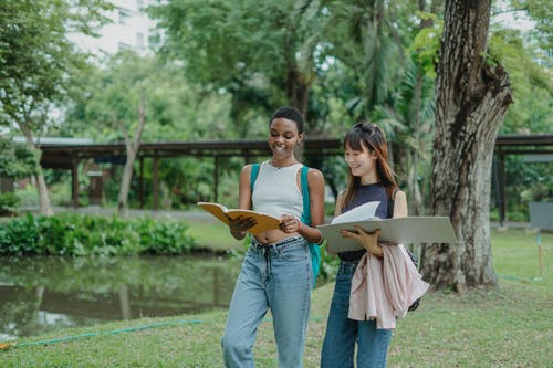 Smiling young multiethnic girlfriends speaking with each other while walking in green park with backpack and notepads in summer day
