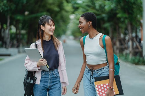 Multiracial female friends talking wile standing on road
