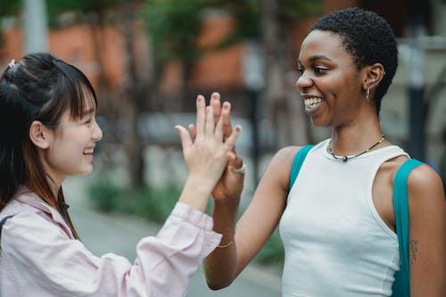 Multiracial women giving high five on street