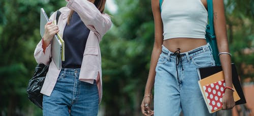 Unrecognizable crop young multiracial women standing in summer day on street with notebooks and laptop and wearing casual outfit