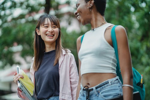 Optimistic smiling diverse female students wearing casual outfits with backpack and laptop strolling together in lush park and discussing term results while looking at each other happily