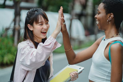 Side view excited multiracial female students in casual clothes giving high five to each other while spending break in lush park