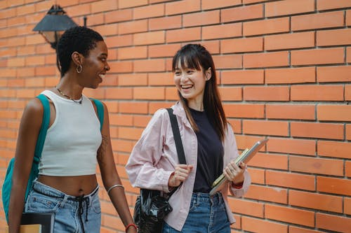 Cheerful multiracial female students wearing casual clothes carrying backpack and notebooks near college brick wall while discussing plans and looking at each other with smiles