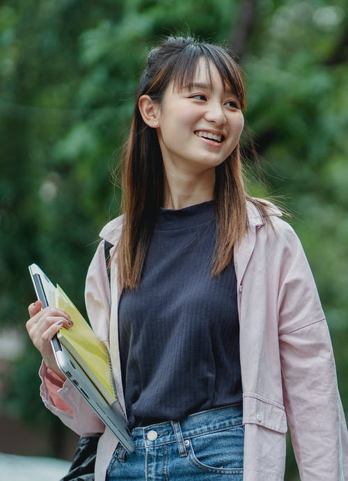 Happy Asian female student waling in park